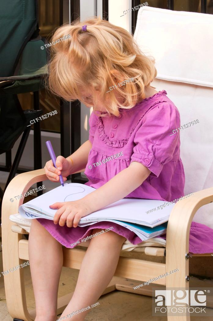 Stock Photo: Young three year old girl drawing on paper with pen.