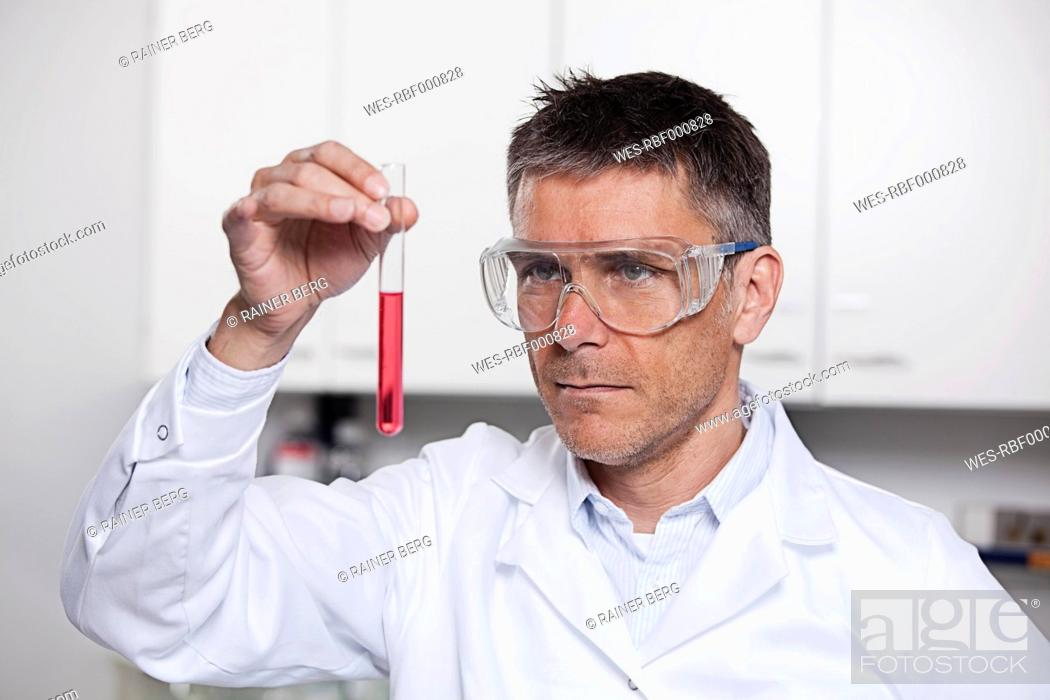 Stock Photo: Germany, Bavaria, Munich, Scientist holding red liquid in test tube for medical research in laboratory.