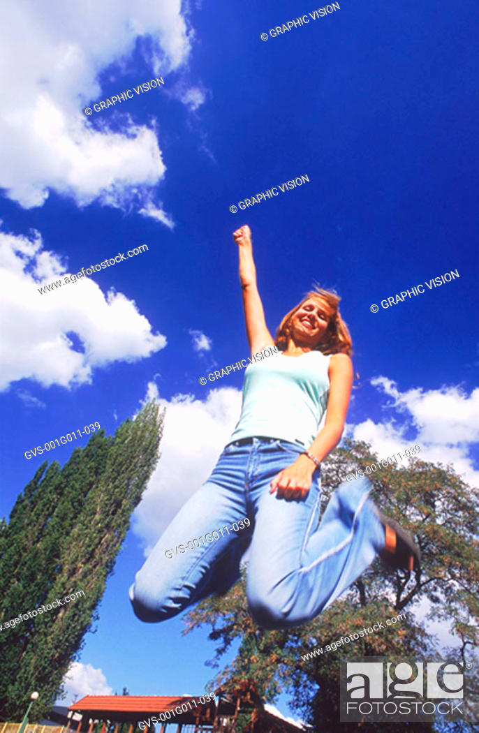 Stock Photo: Low angle view of a young woman jumping up in excitement.