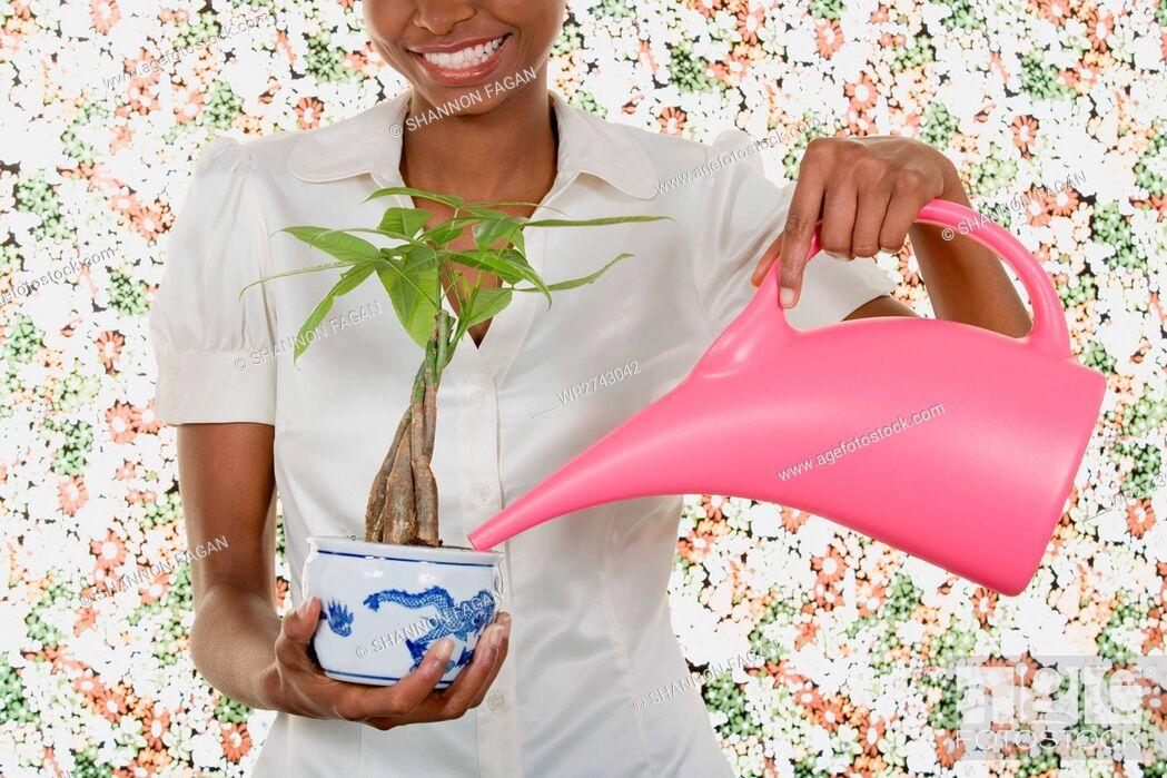 Imagen: Woman watering houseplant.