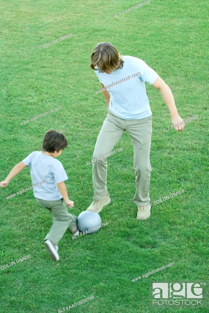 Stock Photo: Young man and boy playing soccer on lawn, high angle view.