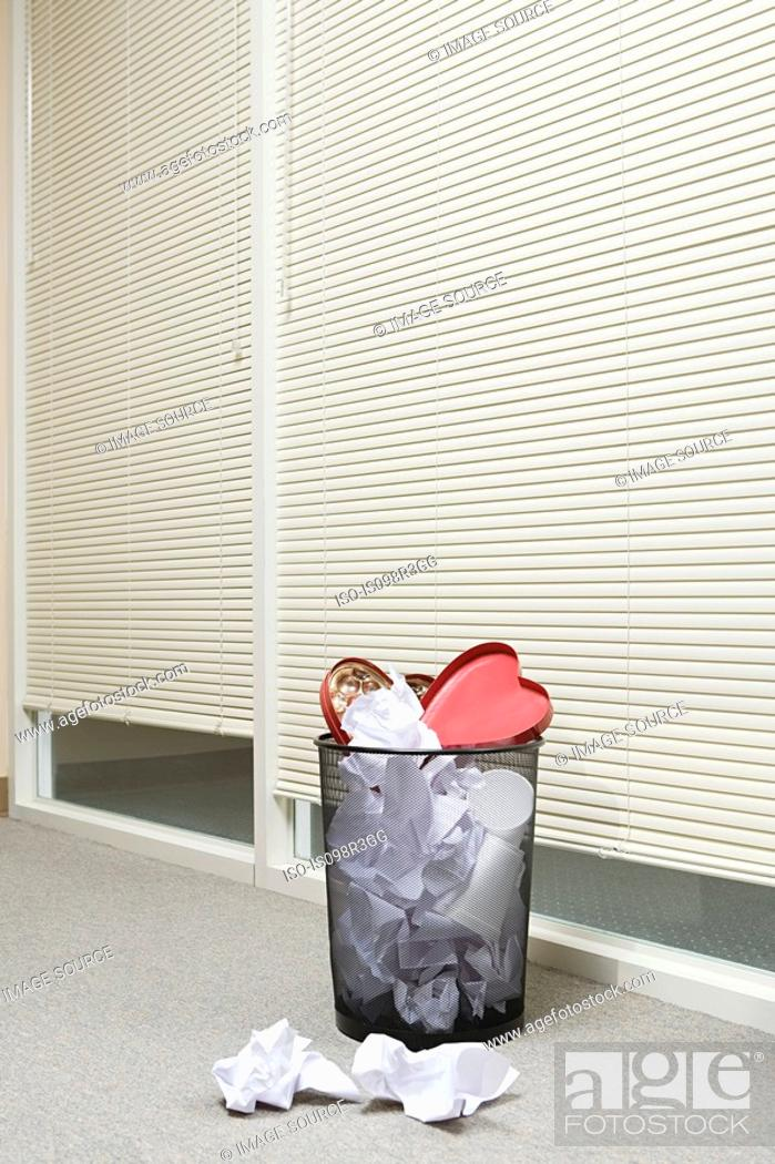 Stock Photo: Office wastepaper basket full of paper and discarded valentines chocolate box.