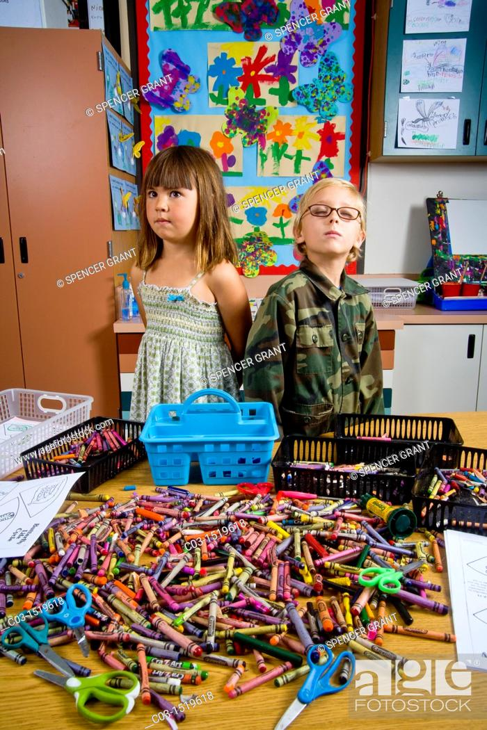 Photo de stock: Kindergarten children in San Clemente, CA, contemplate a table full of classroom objects including crayons and worksheets.