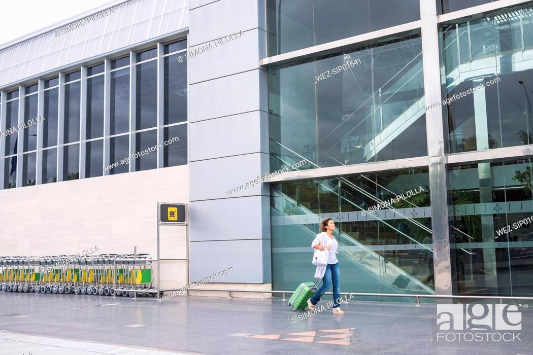 Imagen: Woman walking with rolling suitcase outside airport building.