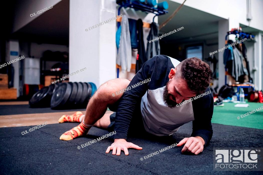 Imagen: Young man stretching legs in gym.