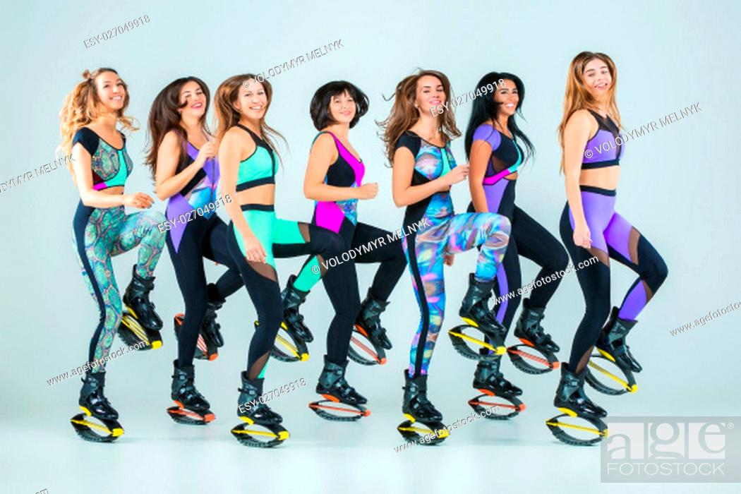 Stock Photo: The group of young girls, jumping on kangoo training on gray.