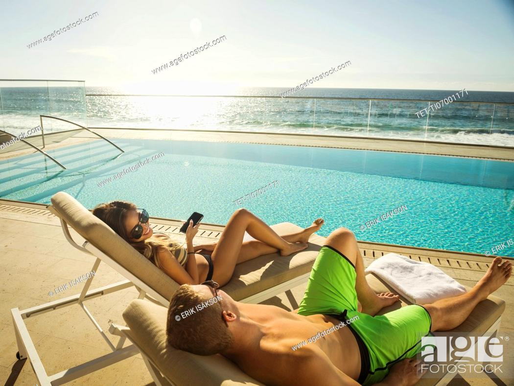 Imagen: Couple relaxing by swimming pool by ocean.