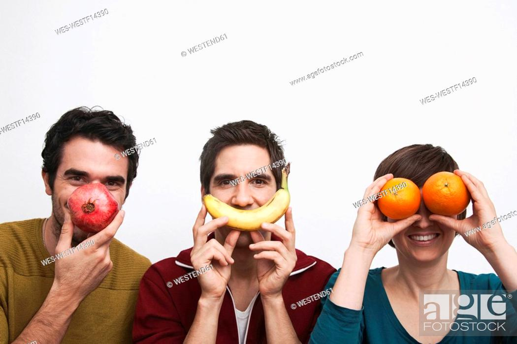 Stock Photo: Men and women holding fruits in front of face.