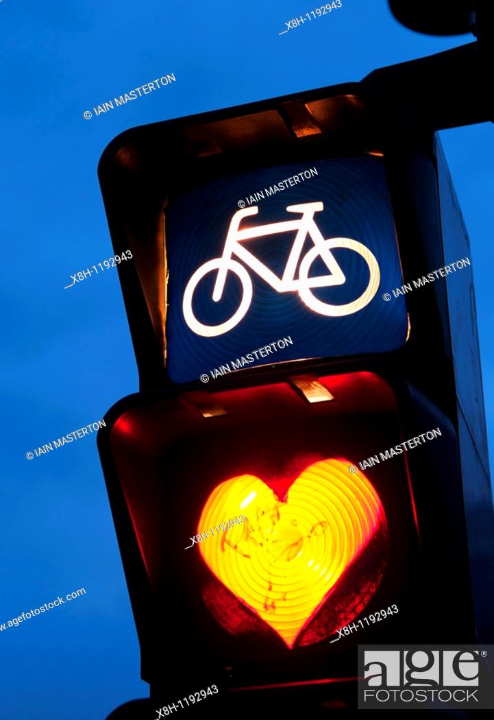Stock Photo: Detail of red cycle traffic stop light painted with love heart in Berlin Germany.