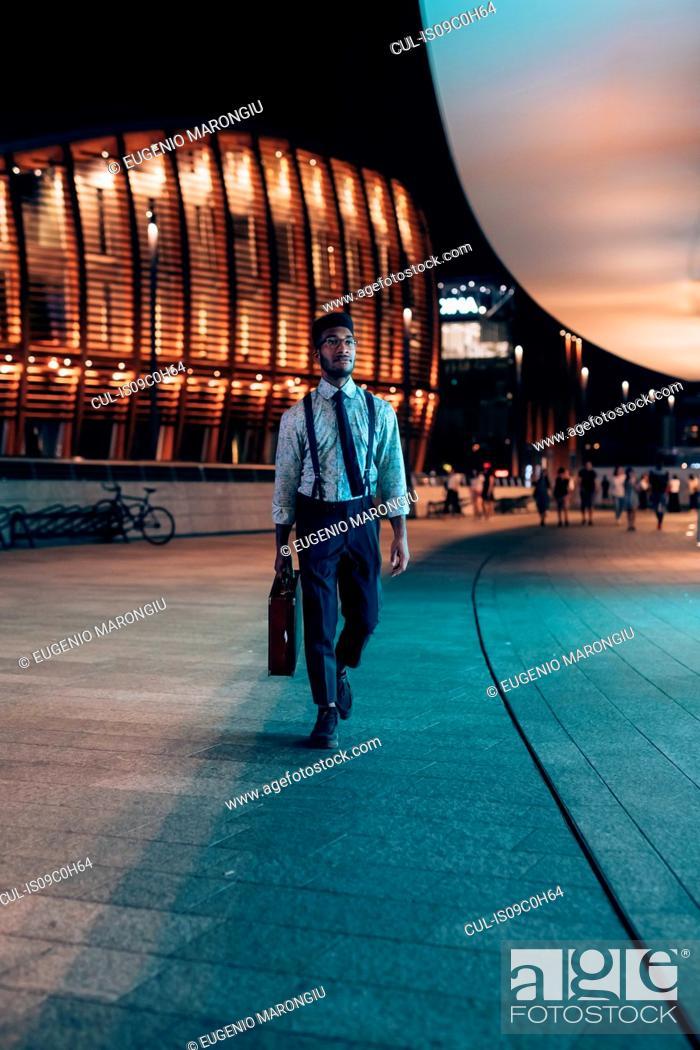 Imagen: Businessman walking past buildings in city, Milano, Lombardia, Italy.