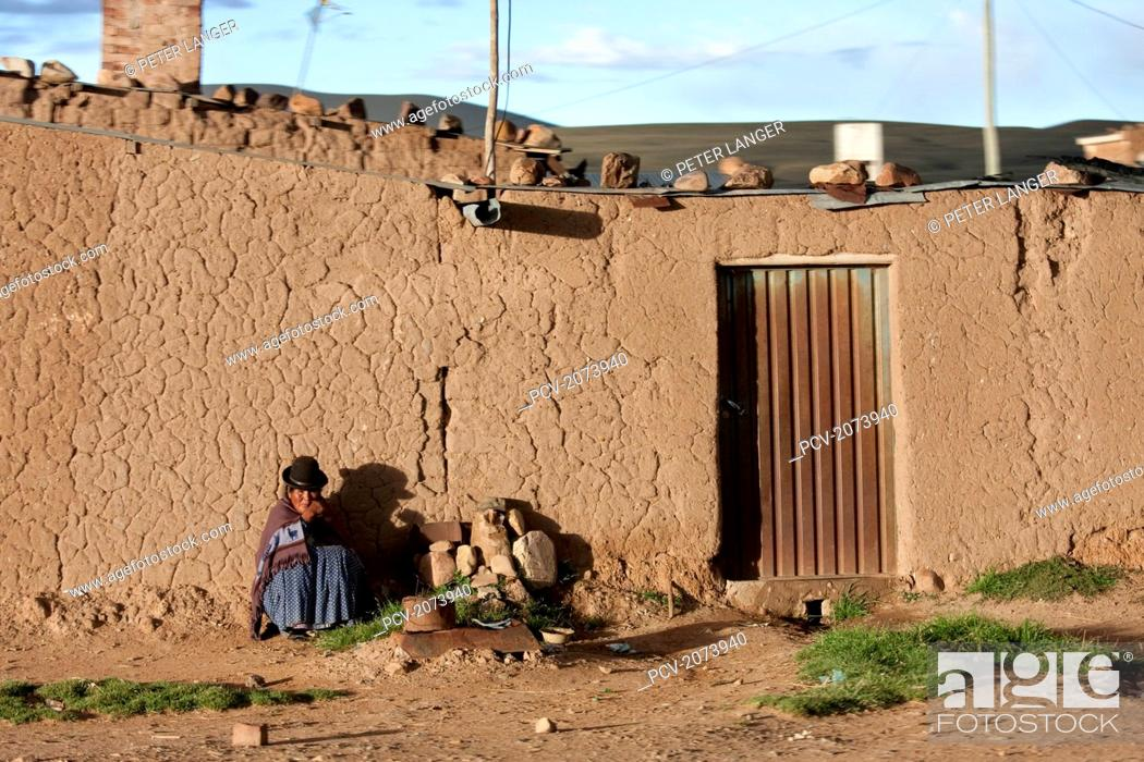 Stock Photo: Aymara Woman Sitting In Front Of An Adobe House By The Road Between La Paz And Oruro, Bolivia.