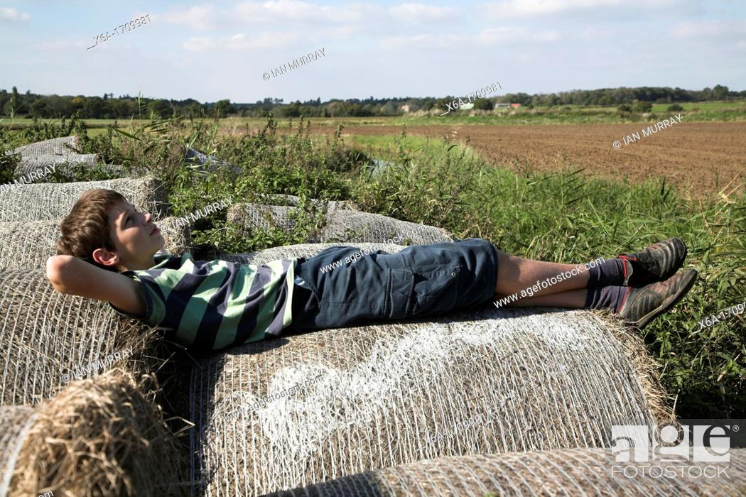 Stock Photo: family picture of boy lying down on straw bales in countryside.