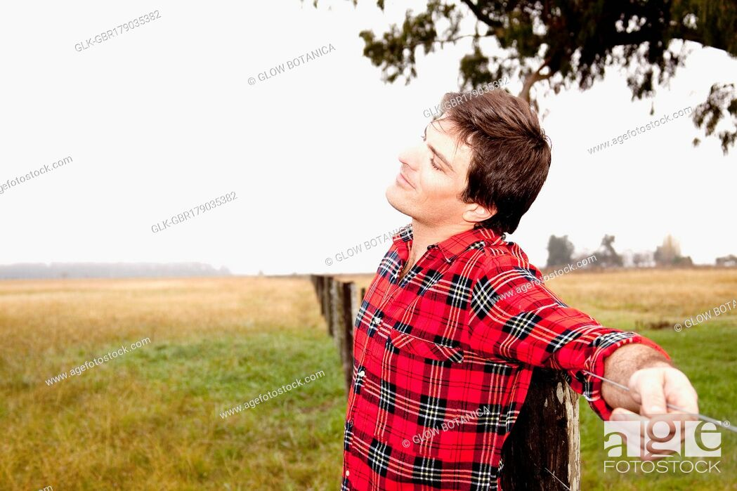 Stock Photo: Man leaning against a fence in a field.