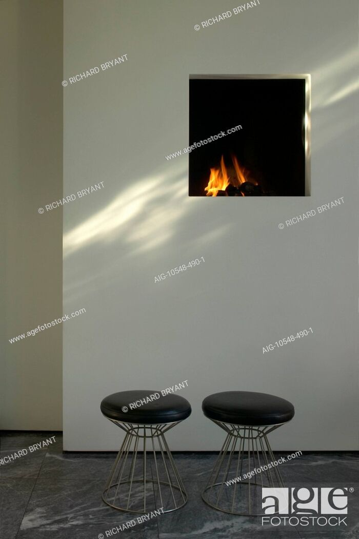 Stock Photo: Refurbished house in Camden Town. Detail of minimalist fireplace in living room. Architect: Munkenbeck and Marshall. Ou Bankoli stools in Connelly leather and.