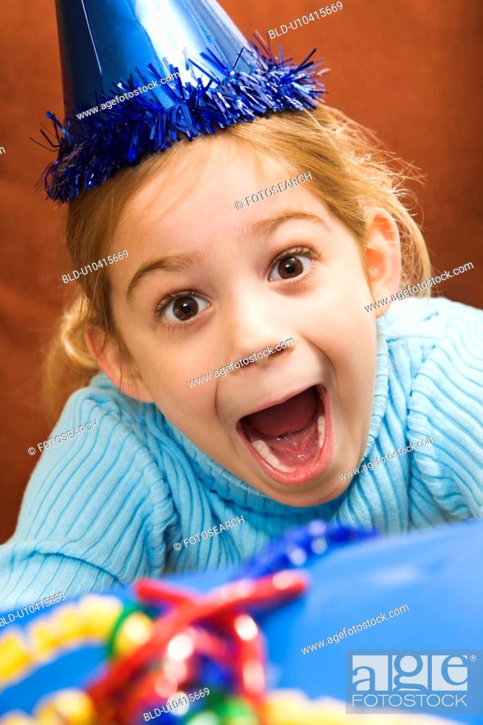 Stock Photo: Caucasian girl wearing party hat holding gift and looking at viewer with excited expression.