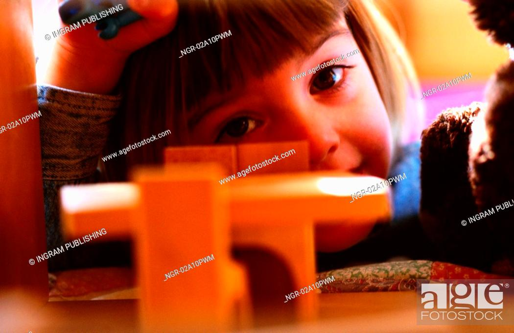 Stock Photo: little girl playing with toy furniture.