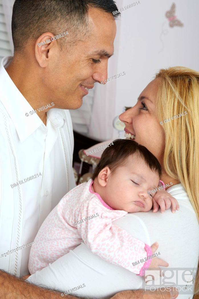 Stock Photo: Hispanic parents holding baby daughter.
