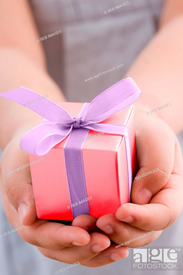 Stock Photo: Girl holding a small gift.