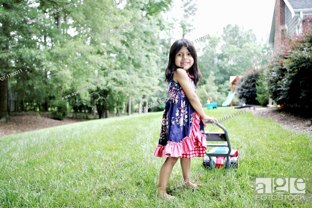 Stock Photo: A young girl with a toy lawn mower pretending to mow the lawn.