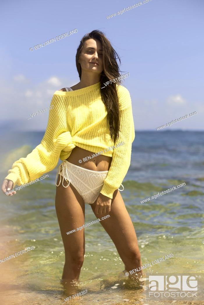 Stock Photo: Young woman at beach in a yellow sweater. Crete, Greece.