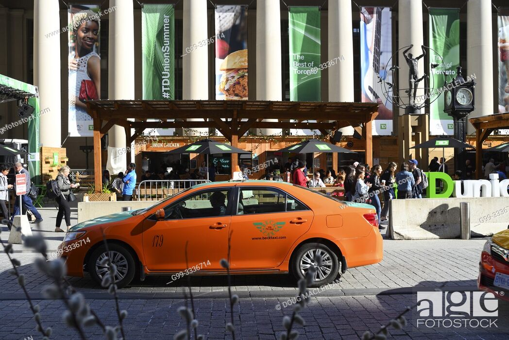 Stock Photo: An orange taxicab in front of a temporary, summer-long food and beverage festival at rushhour in front of Union Station, Toronto, Ontario, Canada.