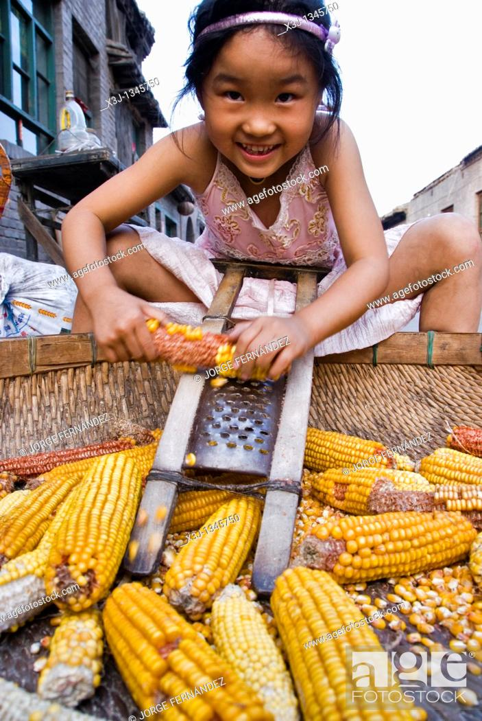 Stock Photo: Girl taking the grain out of the corncobs in the street  Pingyao, Shanxi, China.
