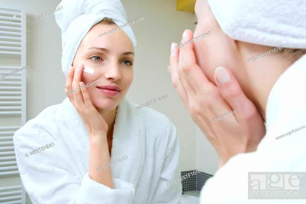 Stock Photo: Young woman applying beauty cream.