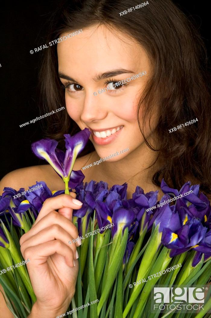 Stock Photo: young woman smelling blue iris.