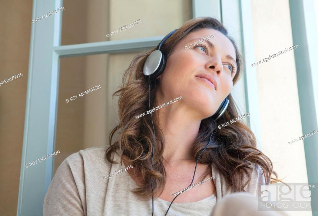 Stock Photo: Calm woman listening to music on headphones in window.