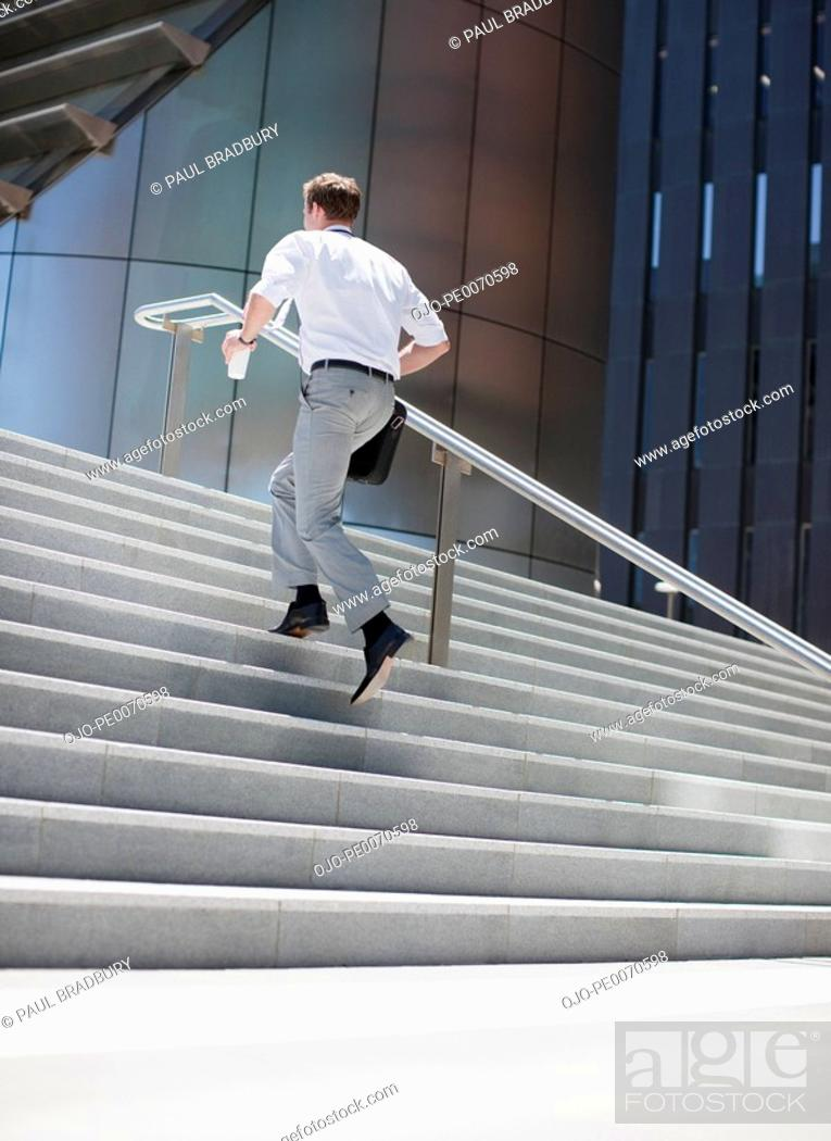 Stock Photo: Businessman rushing up steps outdoors.