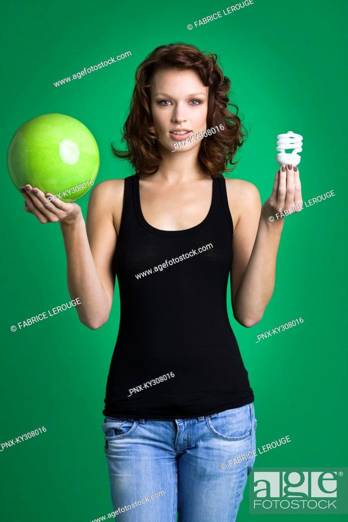 Stock Photo: Young woman holding green ball and light bulb.