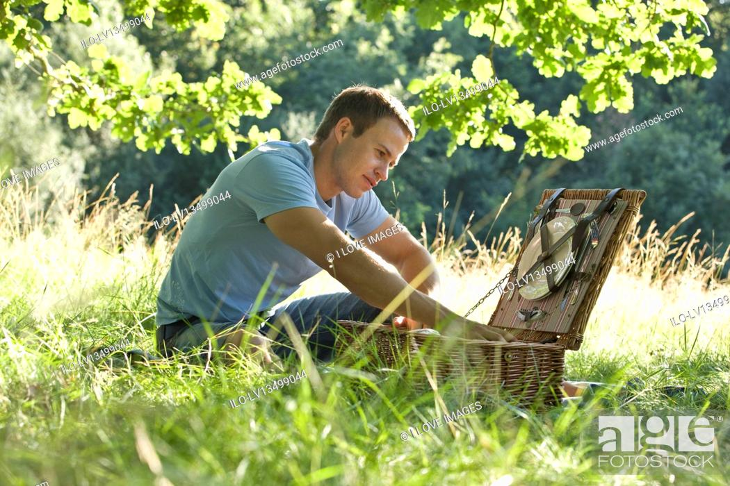 Stock Photo: A young man opening a picnic basket.