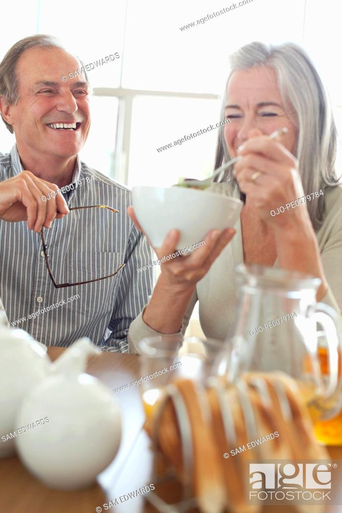 Stock Photo: Senior couple laughing at breakfast.