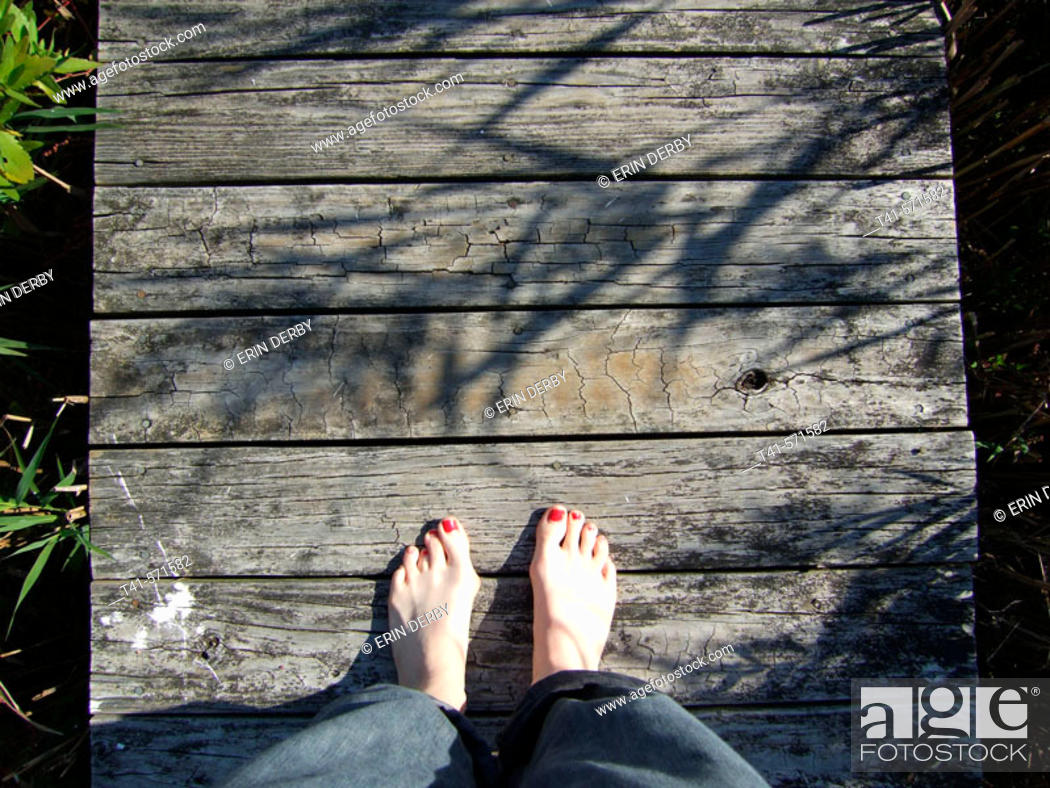 Stock Photo: Bare feet on a dock in Mattituck, NY. Mattituck is on the South Shore of the North Fork of Long Island. The feet are of a woman, with half worn polish.