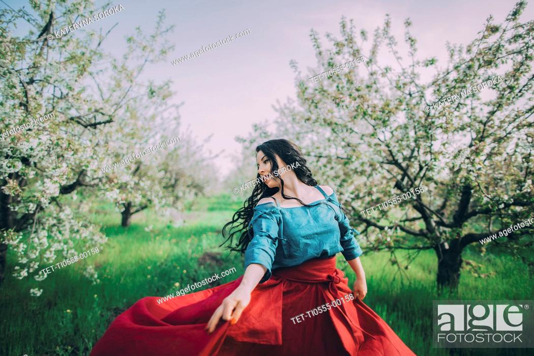 Stock Photo: Young woman dancing in blooming orchard.