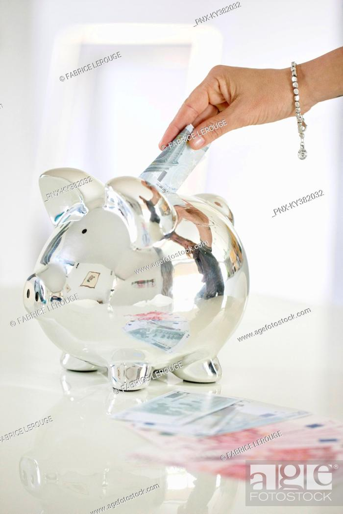 Stock Photo: Person's hand putting money into a piggy bank.