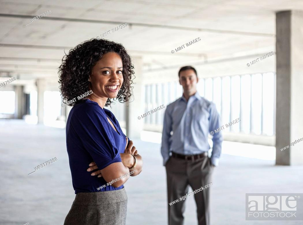 Stock Photo: Mixed race team of business people in a large empty raw office space.
