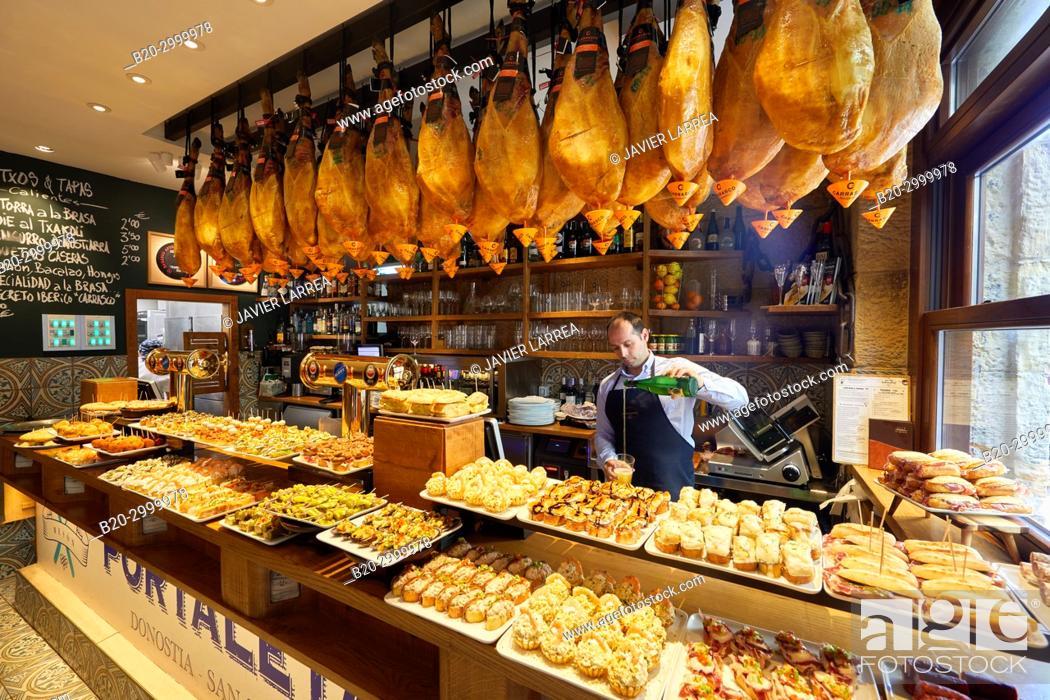 Imagen: Waiter serving txakoli wine, Ham, Pintxos, Bar Restaurante Portaletas, Parte Vieja, Old Town, Donostia, San Sebastian, Gipuzkoa, Basque Country, Spain.
