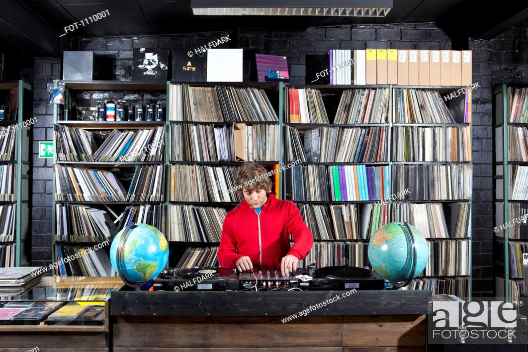 Stock Photo: A young man using a sound mixer and DJ decks at a record store.