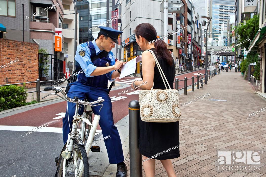Imagen: Policeman on bicycle helps pedestrian locate address in Roppongi, Tokyo, Japan.