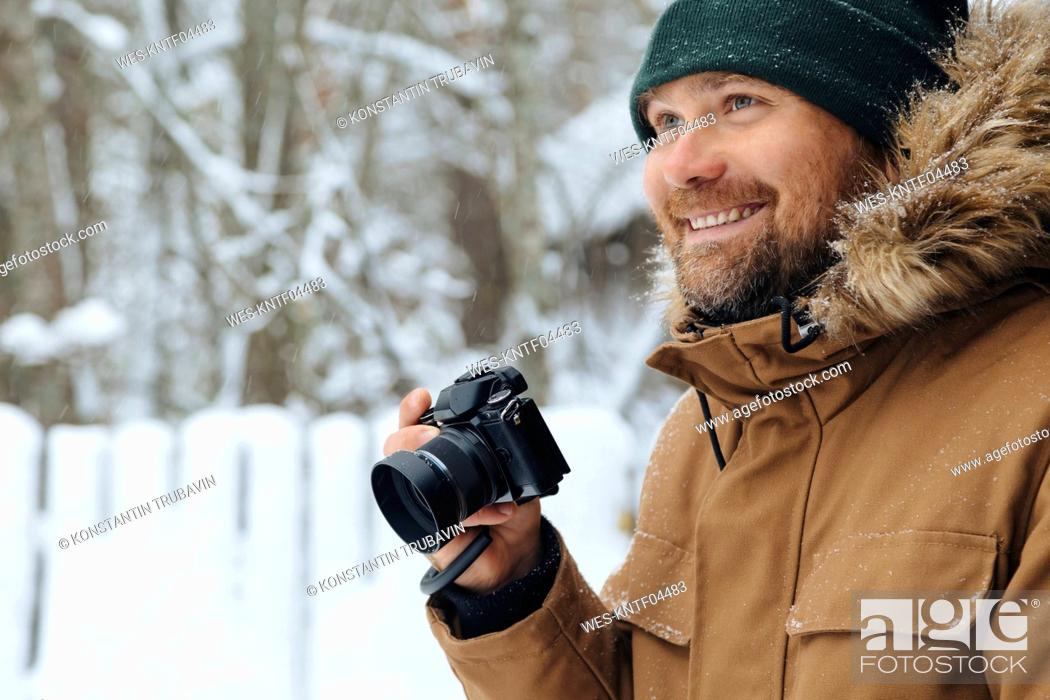 Photo de stock: Portrait of happy man with digital camera in winter.
