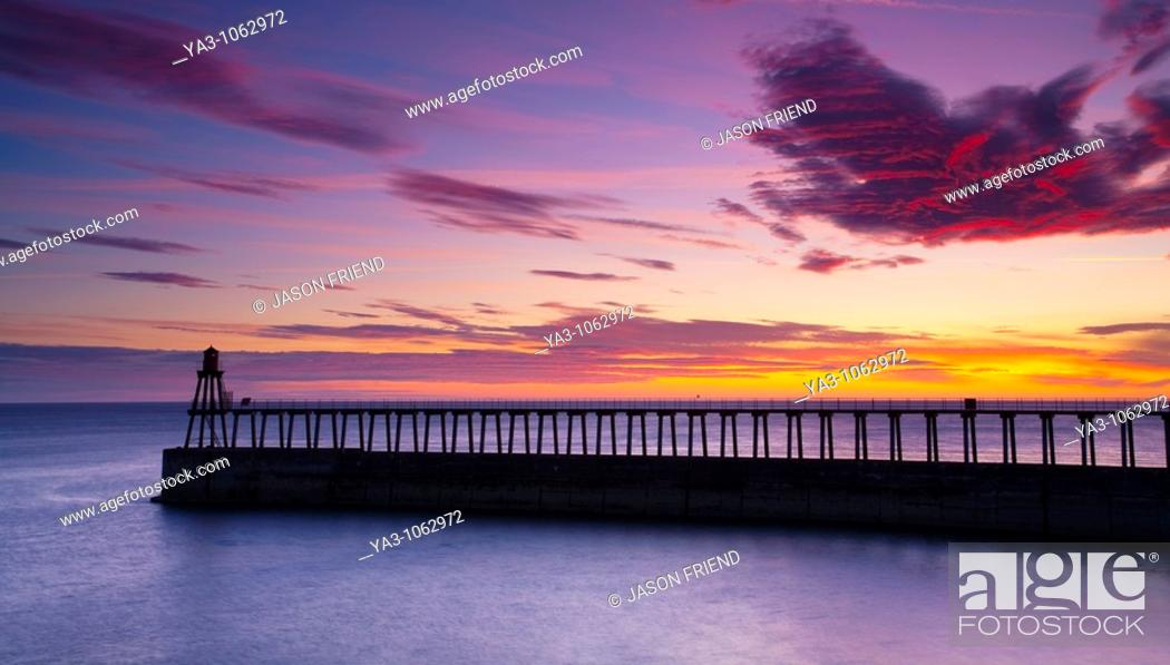 Stock Photo: England, North Yorkshire, Whitby  One of the entrance piers of Whitby Harbour at dawn.