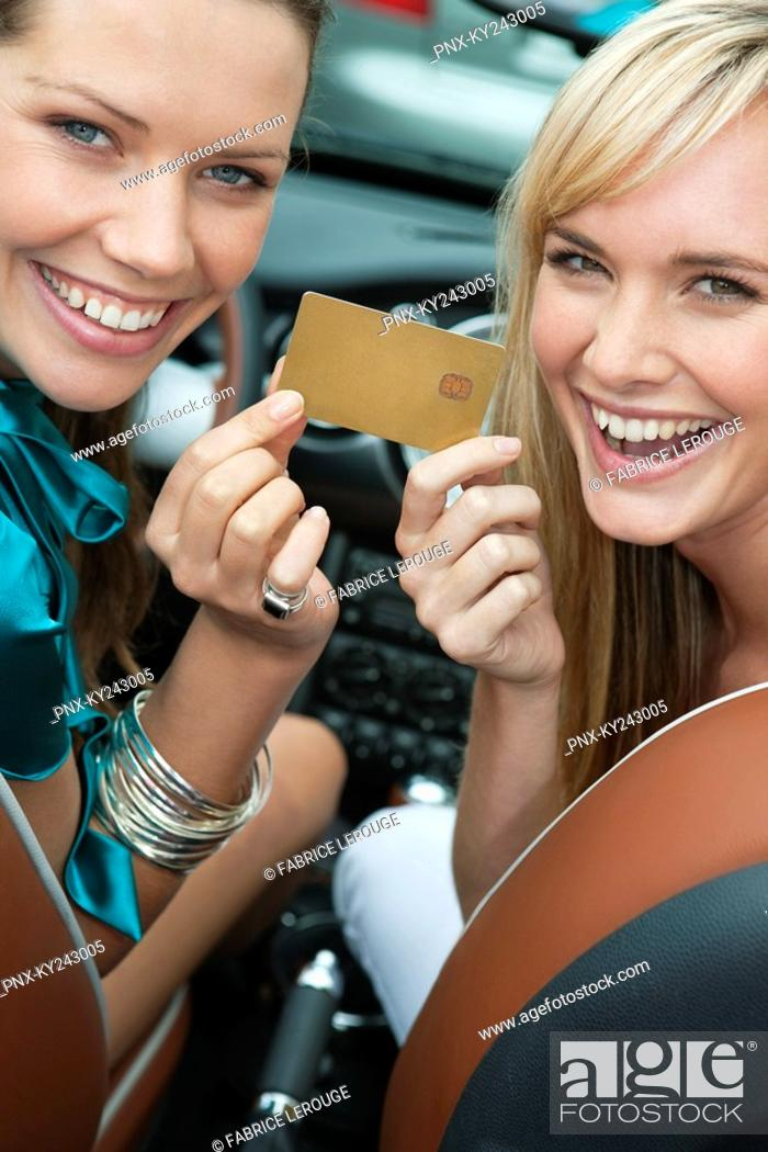 Stock Photo: Two women showing a credit card in a car.