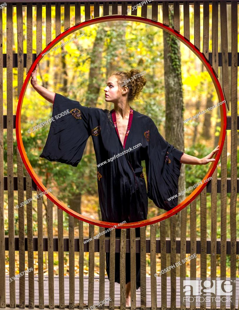 Stock Photo: A 28 year old blond woman dressed in a kimono by a Japanese style moon window.