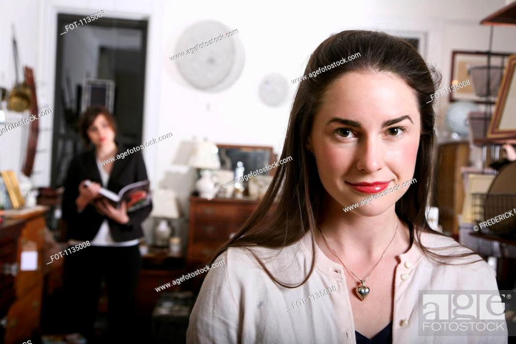 Stock Photo: A smiling woman standing in an antiques shop.