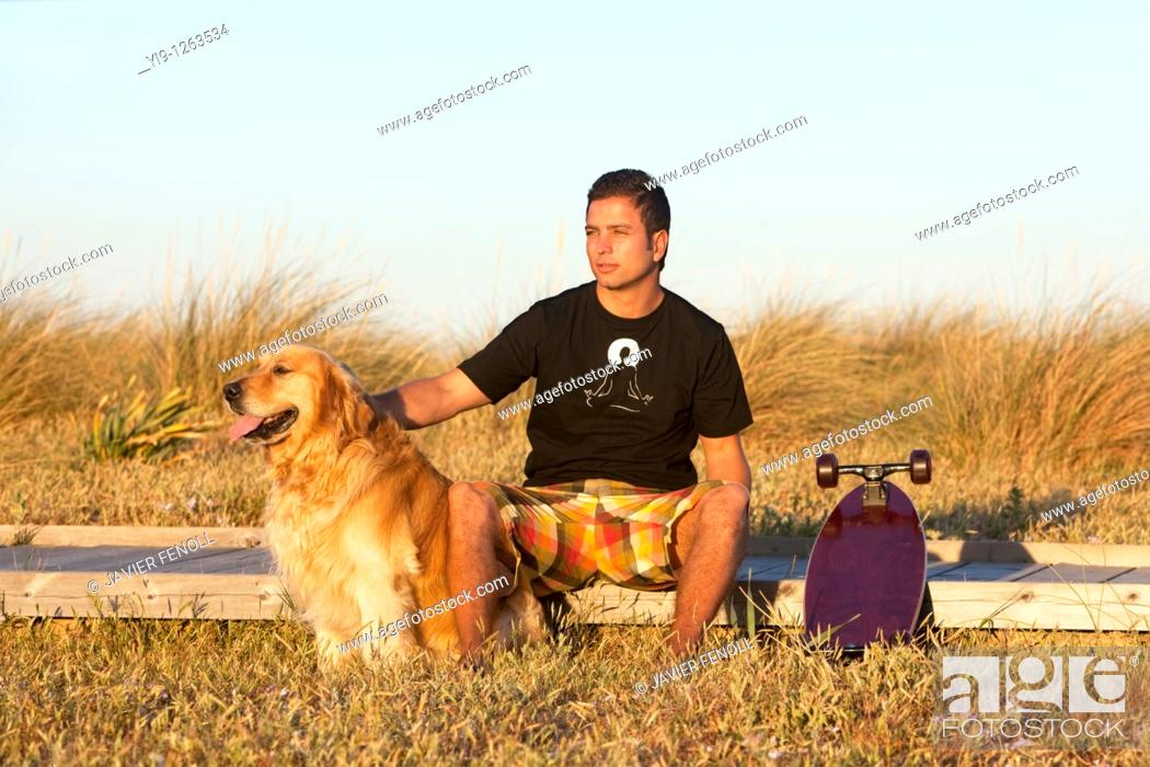 Stock Photo: Young Male posing with his skate board and his dog.