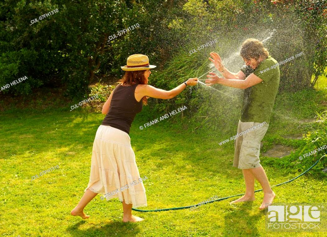 Stock Photo: Woman spraying man with garden hose.