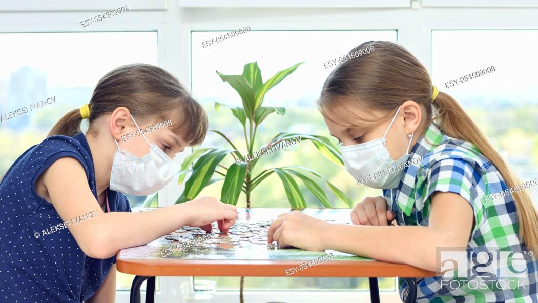Stock Photo: Two girls in medical masks sit at a table and play board games.