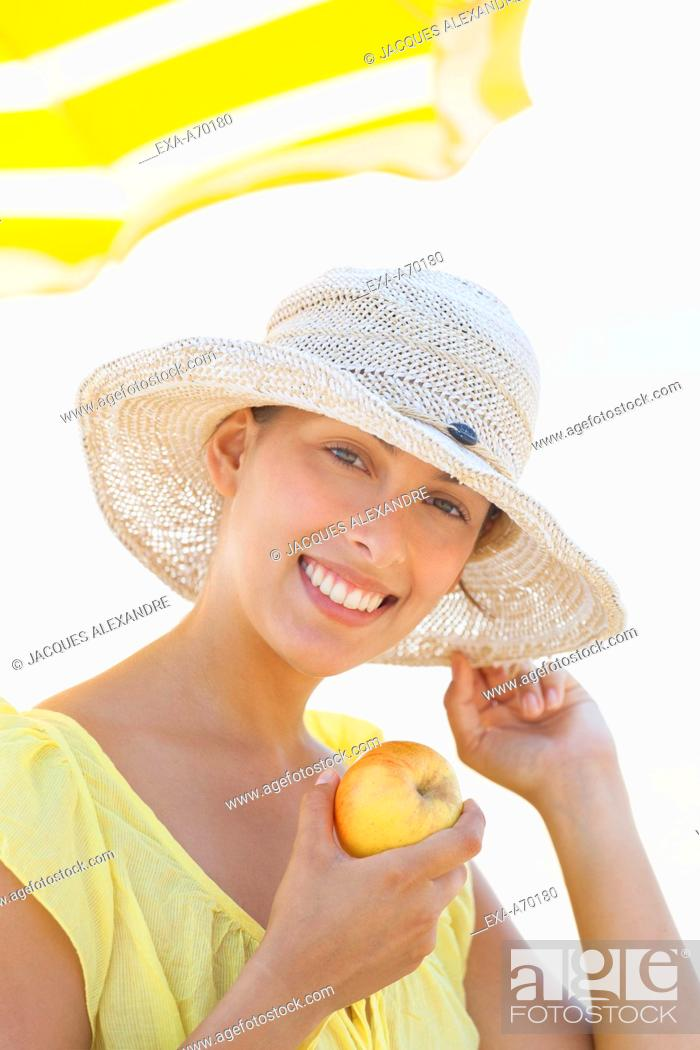 Imagen: woman at beach with sun hat.