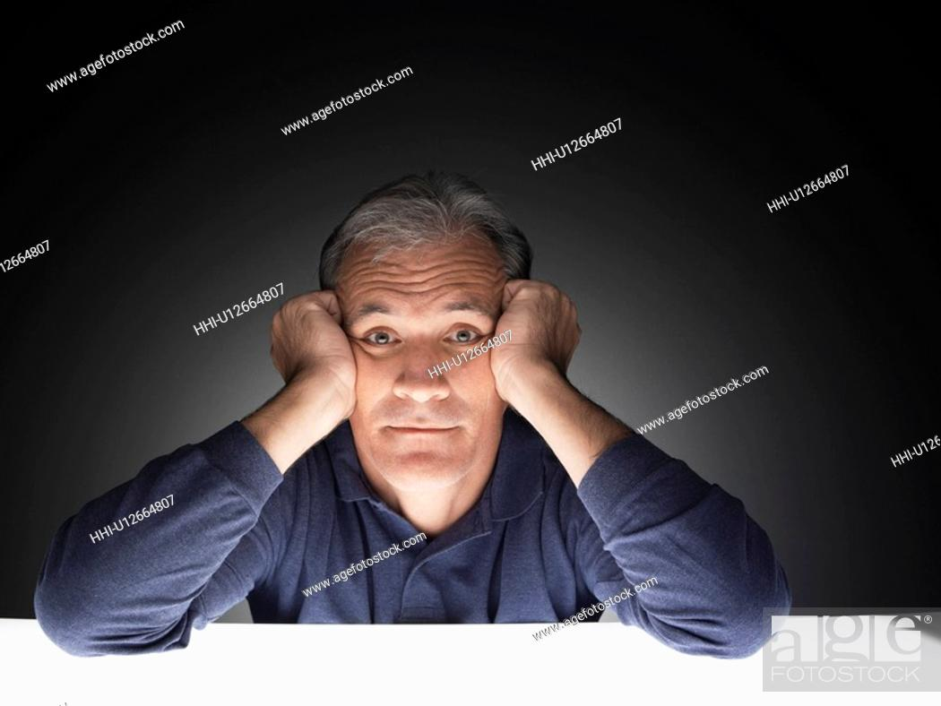 Stock Photo: Mature man with head in hands (portrait).